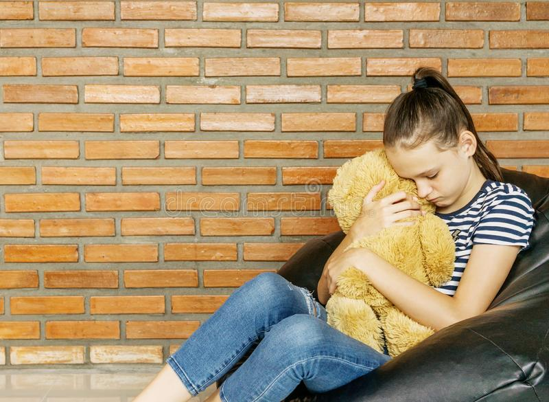 Upset caucasian teen girl sitting in black bean bag chair hug big brown teddy bear toy against brick wall. Casual outfit. Sadness royalty free stock photos