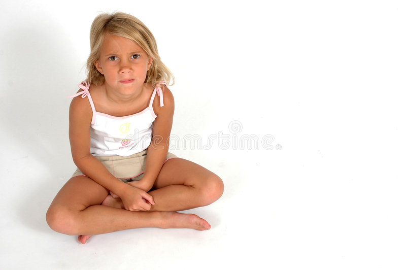 Upset Child. Child sits cross legged with questionable look on her face. She is mad and does not understand stock photo