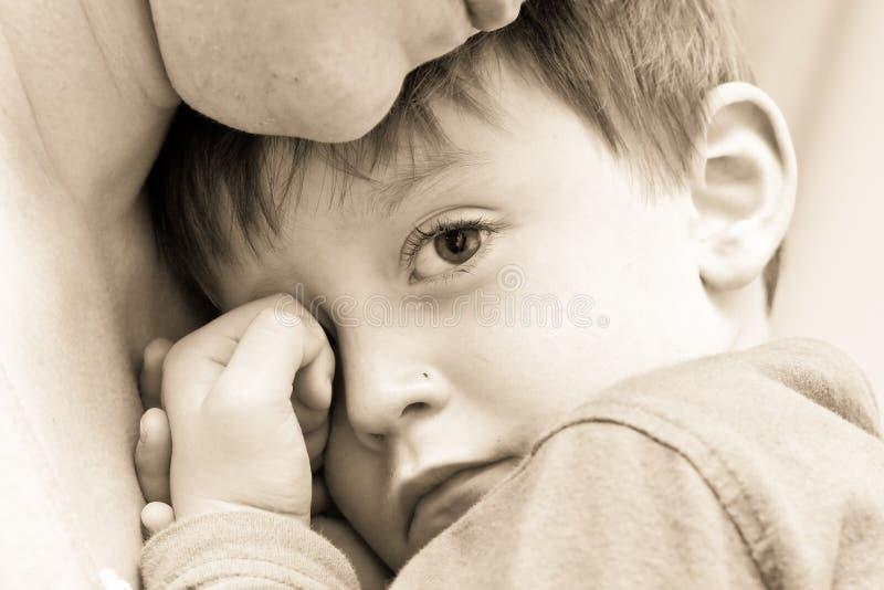 Upset child. Nice image of a young upset boy cuddling his mum stock photo