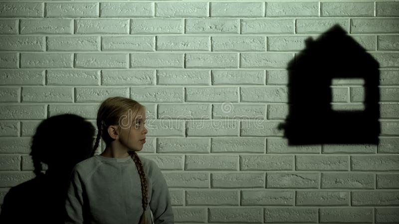 Upset child watching house shadow, homeless kid dreaming about home and family. Stock photo stock photo