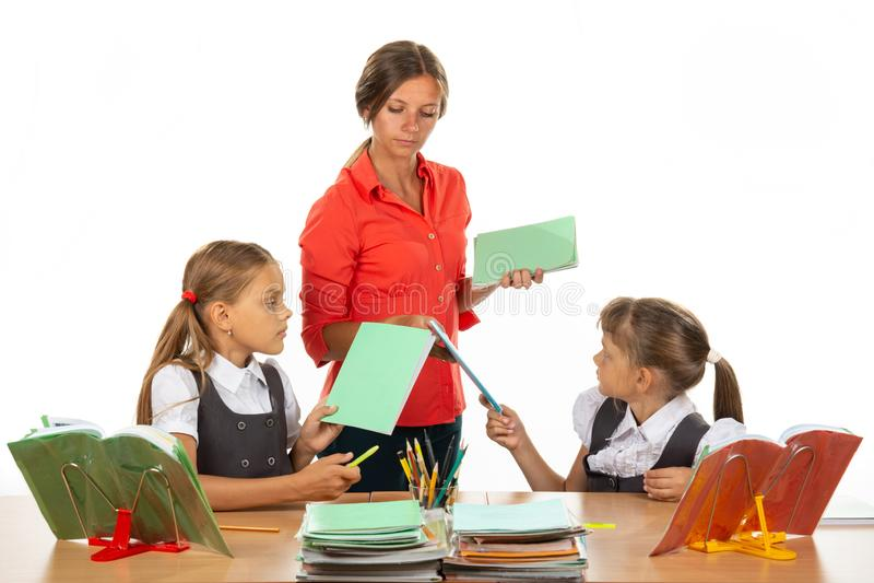 Upset children hand over notebooks to teacher royalty free stock image