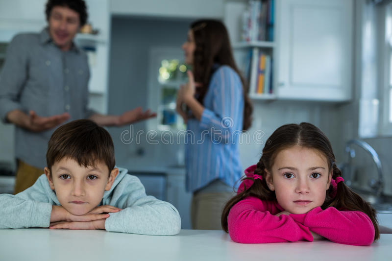 Upset children sitting while couple arguing with each other. In the kitchen stock photos