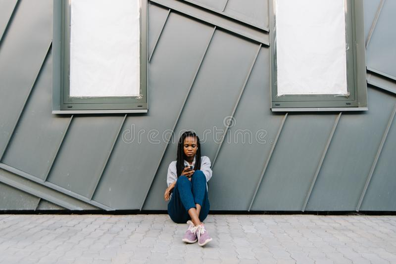 Upset confident african woman is texting and browsing o nt he mobile phone while sitting on the ground and leaning on stock photography