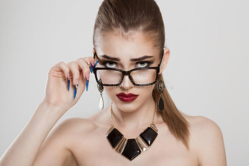 Upset confused woman holding her glasses down to see what`s going on stock photography
