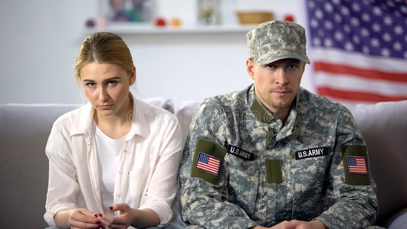 Upset couple of american soldier and his wife sitting on sofa, risk of break-up. Stock photo stock photos