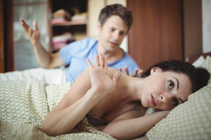 Upset couple arguing with each other on bed. In bedroom royalty free stock image