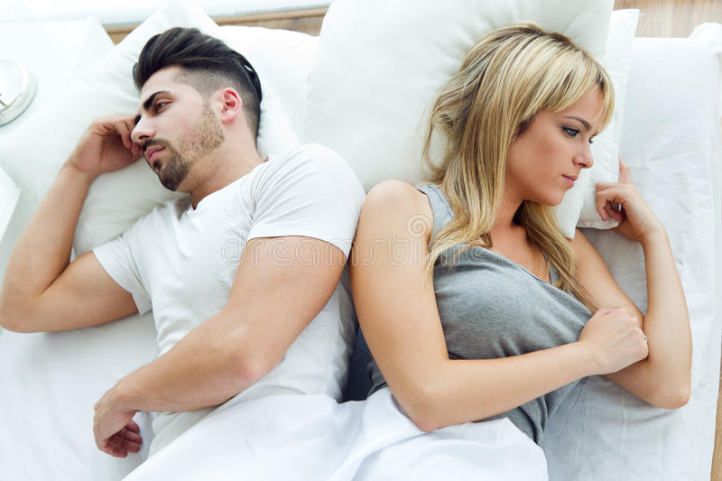 Upset couple lying back to back in bed royalty free stock photos