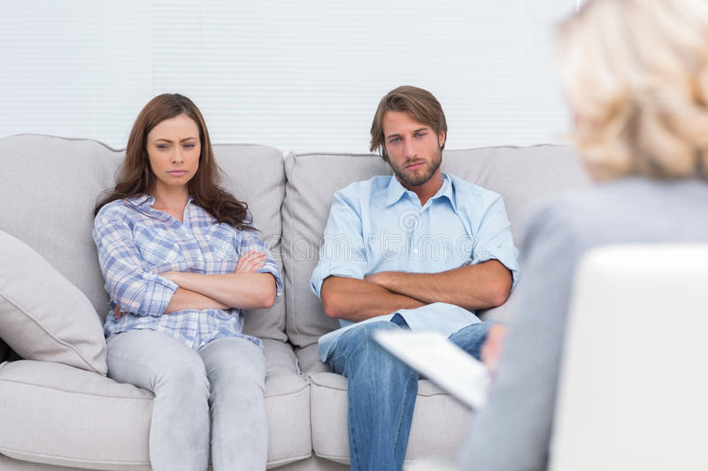 Upset couple sit on a sofa with arms crossed stock photography