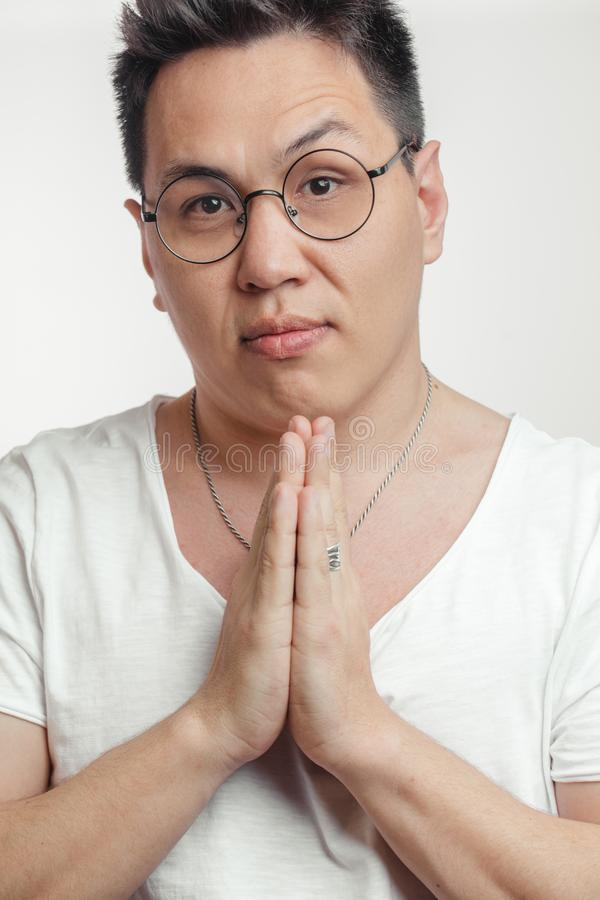 Asian man in t-shirt, holding hands in pray, begging for help or asking apology. Upset cute Asian guy in t-shirt, holding hands in pray and gazing at camera with royalty free stock photography