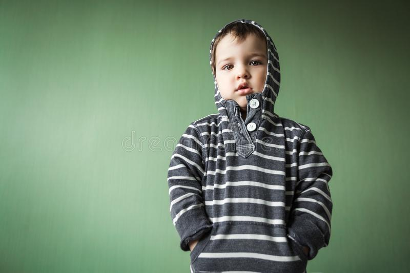 Upset cute young boy holding hands in pockets royalty free stock photo