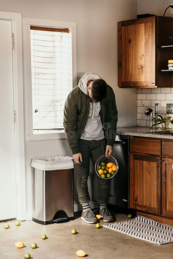Upset and Defeated Young Adult Person Accidentally Spills Basket of Lemons and Lime Fruit All Over Modern Home Kitchen Floor and h royalty free stock photography