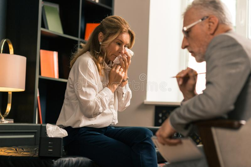 Upset depressed blonde woman complaining to her psychologist royalty free stock image