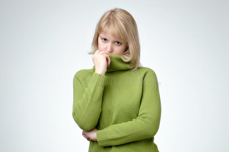 Upset depressed blonde young woman wears green sweater looks sad unhappy royalty free stock photo
