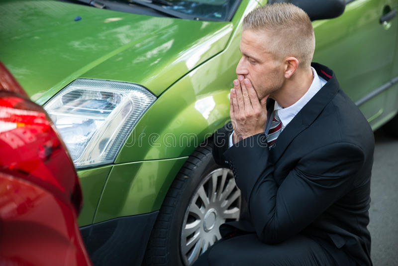 Upset driver looking at car after traffic collision. Upset Driver In Front Of Automobile Crash Car Collision royalty free stock photography