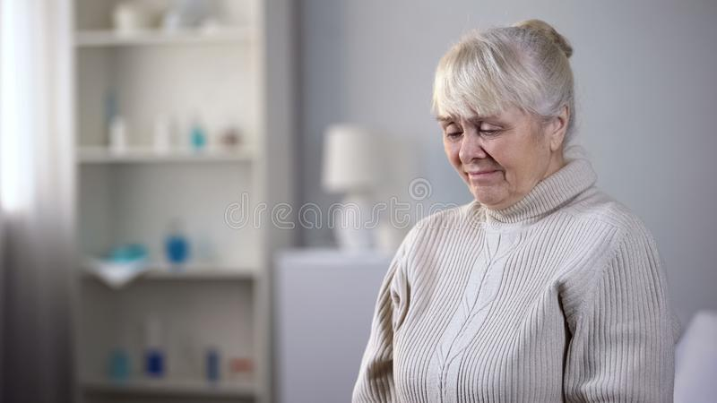 Upset elderly lady sitting alone in nursing house and crying, health problems. Stock photo stock photography