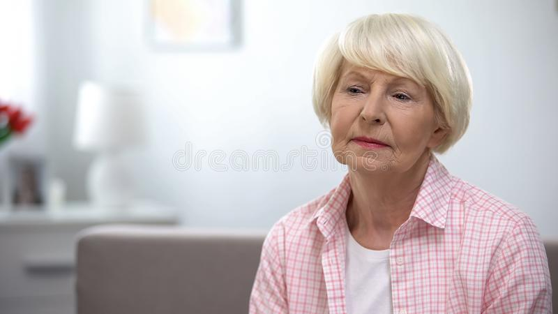 Upset elderly woman sitting alone in nursing home, abandoned by relatives. Stock photo stock images