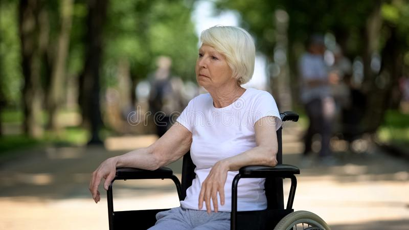 Upset elderly woman sitting in wheelchair at nursing home park, terminal illness stock images