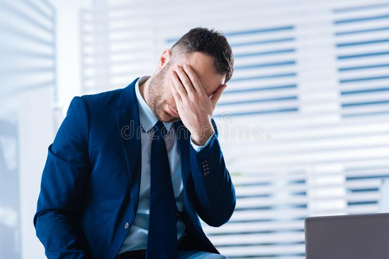 Upset emotional man closing the eyes while understanding his big mistake. Oh no. Emotional hardworking businessman sitting in his office and feeling upset when stock photos