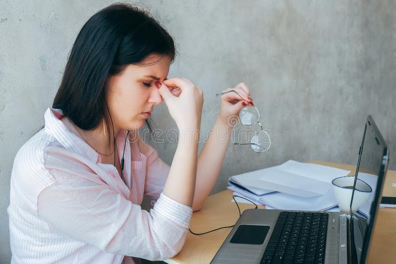 Upset fatigued overworked young business woman taking off glasses tired of computer work, exhausted student suffers from blurry royalty free stock photography