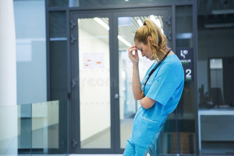 Upset female doctor standing in corridor stock photos