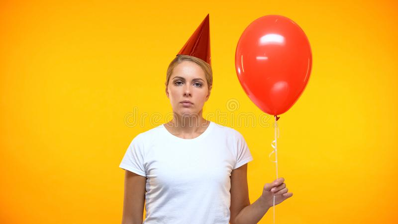 Upset female with red balloon in hand, feeling lonely on birthday party, sadness. Stock photo royalty free stock images