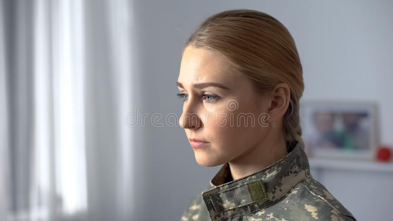 Upset female soldier in military uniform sadly looking in rehab center window stock photos
