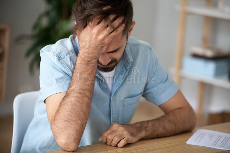 Upset frustrated man holding head in hands, shocked by bad news royalty free stock photography