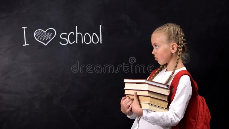 Upset girl with books looking at I love school phrase written on blackboard stock photo