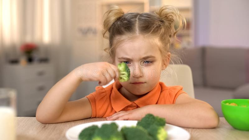 Upset girl looking at broccoli with disgust, full of vitamins but tasteless food stock images