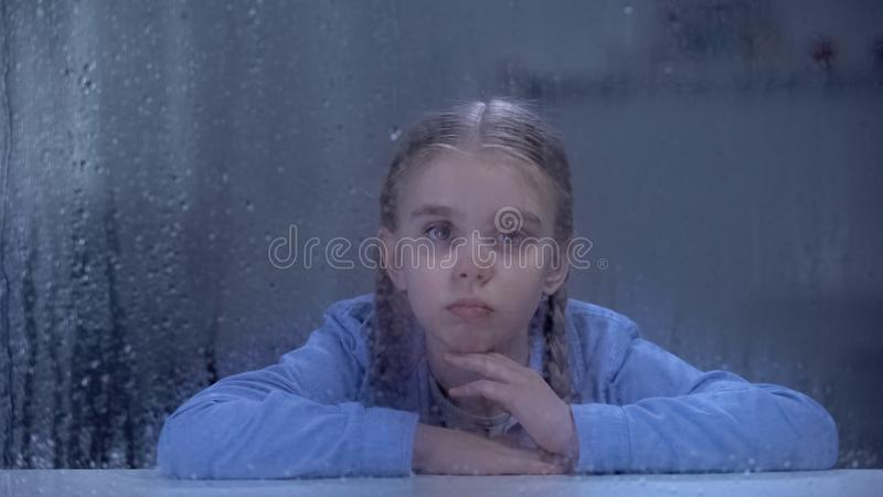 Upset girl looking through rainy hospital window, feeling lonely and insecure. Stock photo stock photos