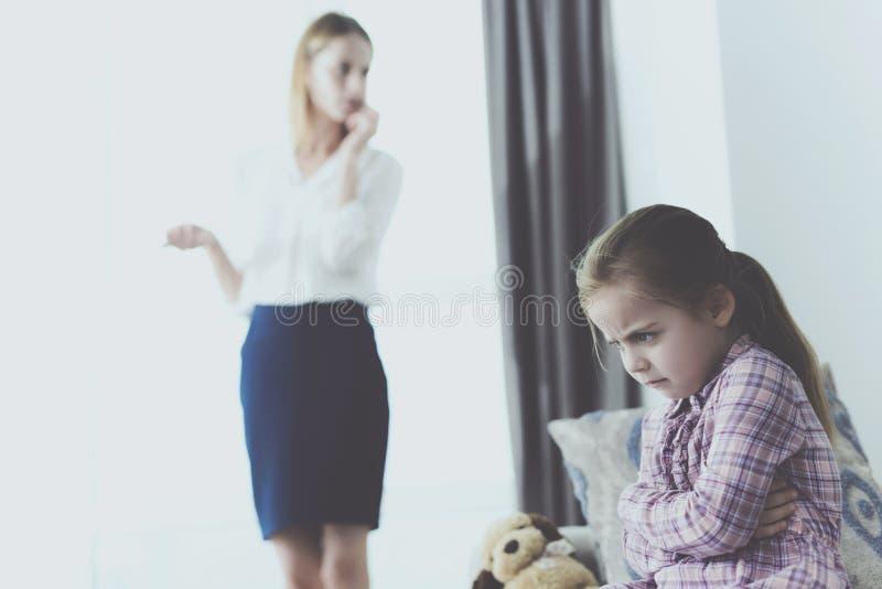 Upset Girl Sitting Indoors when Mother Telephones stock photo
