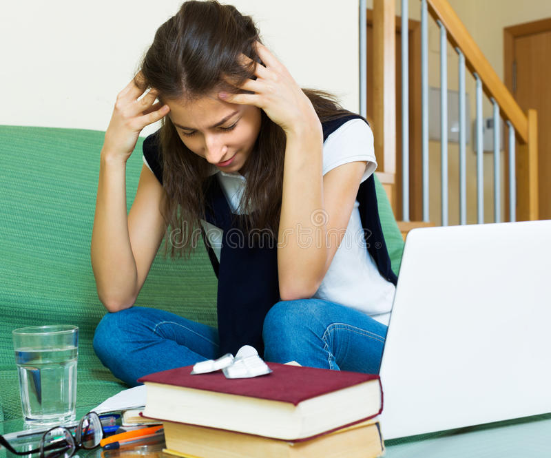 Upset girl study at home. Upset young girl study at home behind her laptop royalty free stock images