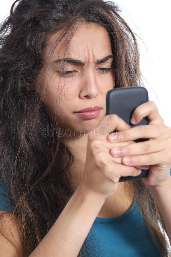 Upset girl with tousled hair having a bad day on the phone. Close up of an upset girl with tousled hair having a bad day on the phone isolated on a white royalty free stock images