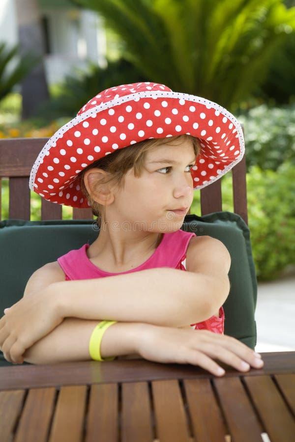 Download Upset Girl Wearing Panama Sitting At Table Stock Image - Image: 10424073