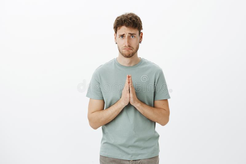 Upset gloomy cute guy with bristle in t-shirt and earrings, holding hands in pray and making sad smile while asking for stock photo