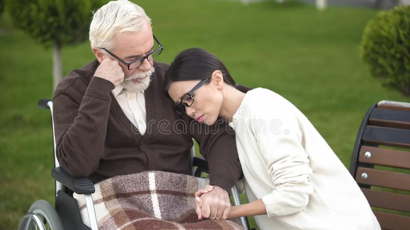 Upset granddaughter sitting near depressed old male, bad diagnosis, dementia stock photography