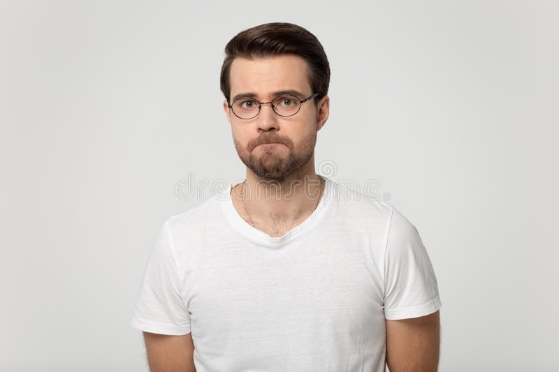 Upset guy with pursed lips posing isolated on gray background. Millennial guy wearing glasses feels upset frustrated or offended with pursed lips posing isolated stock photography