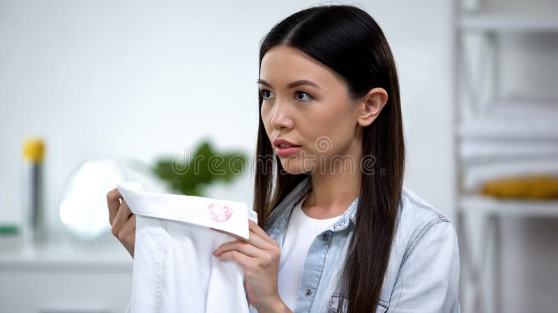 Upset housewife holding shirt with womans lipstick on collar, husbands betrayal. Stock photo royalty free stock photography