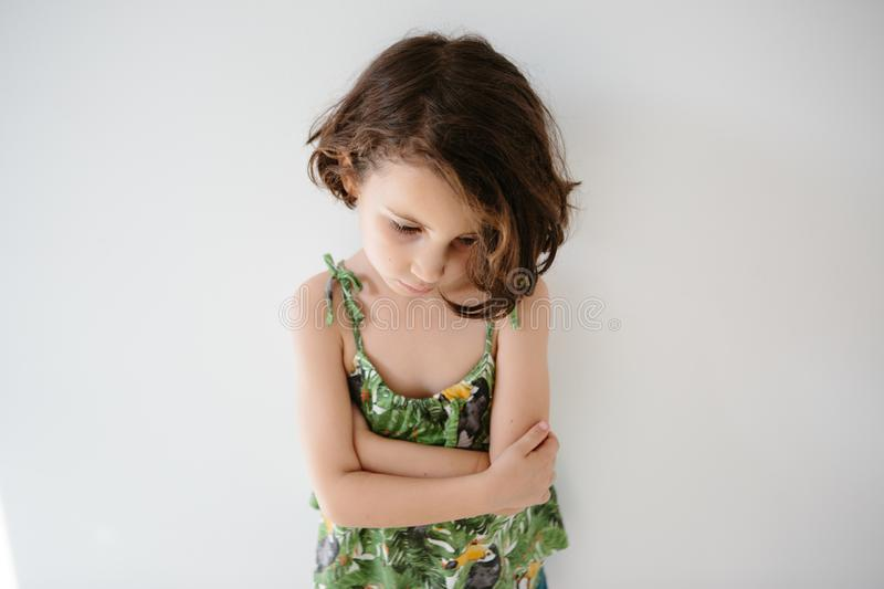 Upset kid leaning on white wall stock image