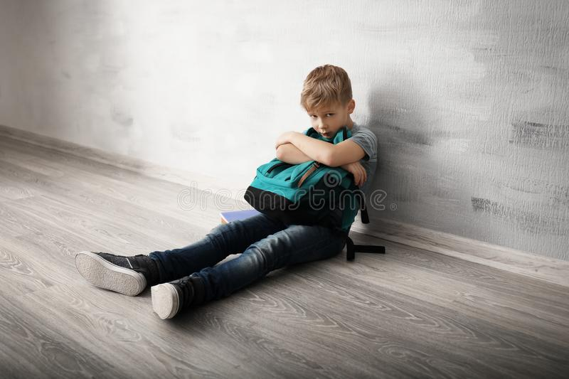 Upset little boy with backpack sitting on floor indoors . Bullying in school stock image