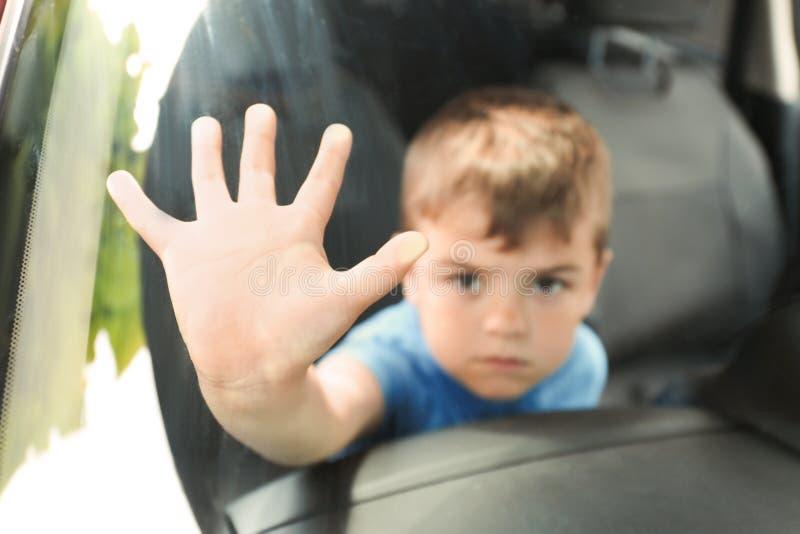 Upset little boy closed inside car, closeup. Child in danger stock photos