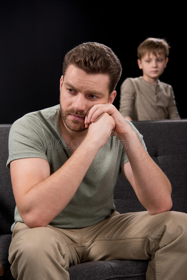 Upset little boy looking at pensive father sitting on sofa and looking away royalty free stock photo