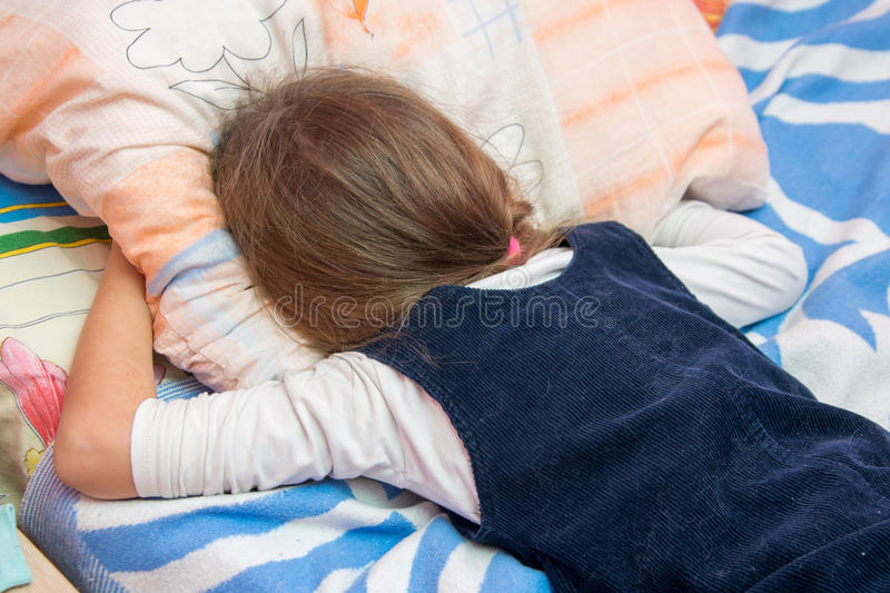 Upset little girl crying with his face buried in pillow royalty free stock photo