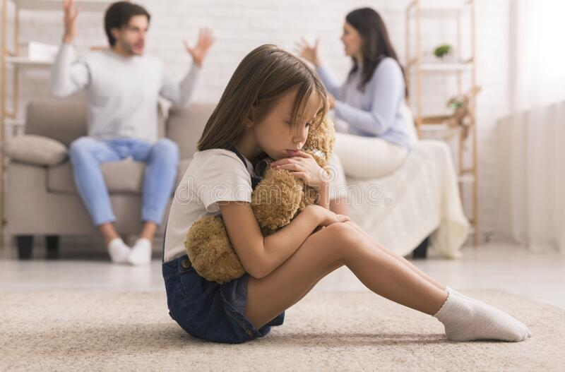 Upset Little Girl Cuddling Teddy Bear, Suffering From Parents Arguing. Family Problems. Cute Little Girl Suffering From Parents Arguing, Sitting On Floor With royalty free stock photo