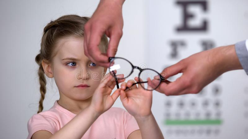 Upset little girl rejecting glasses, child feels insecure in eyewear, discomfort. Stock photo royalty free stock photography