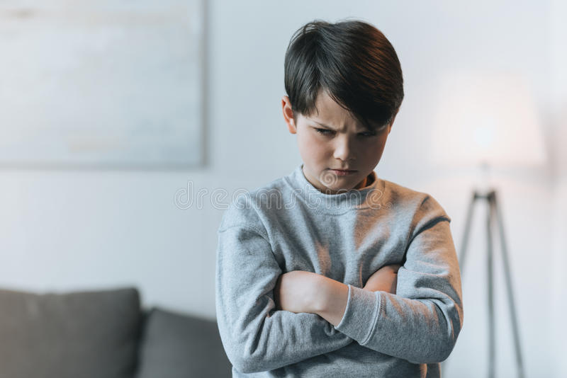 Upset little kid boy with arms crossed stock photos