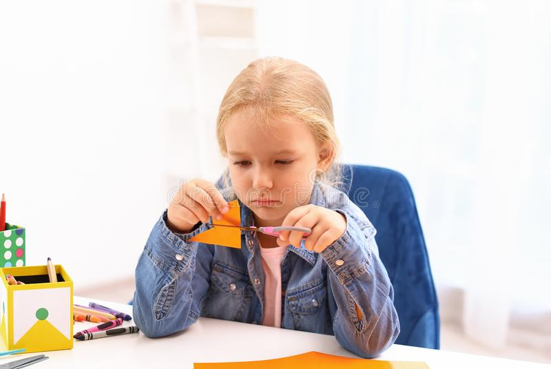 Upset little left-handed girl cutting orange color card at table. Upset little left-handed girl cutting orange color card with scissors at table royalty free stock photography
