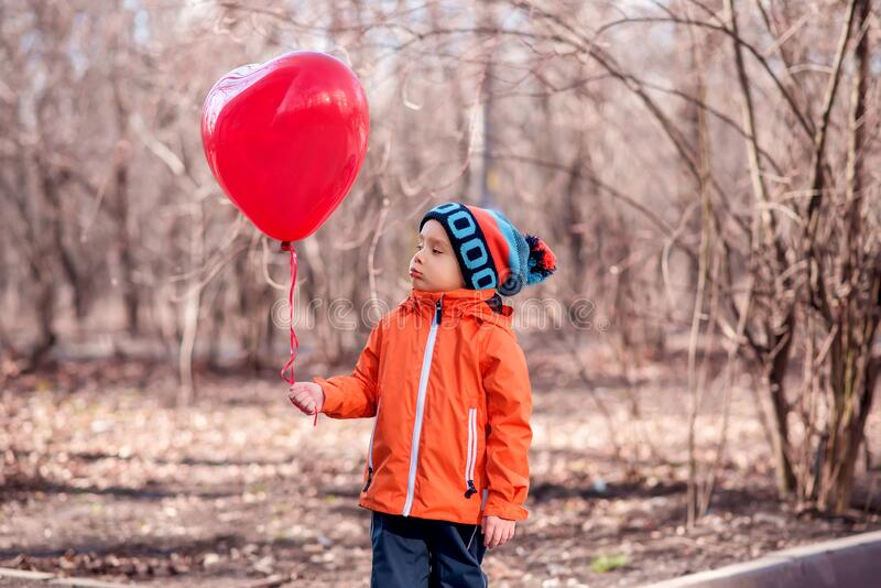 Upset little toddler child in orange jacket standing with unhappy face expression looking at big red heart-shaped balloon stock images