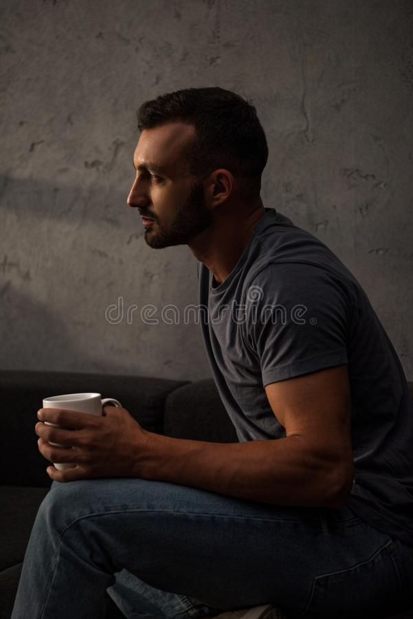 Upset lonely man holding coffee cup. At home stock photography
