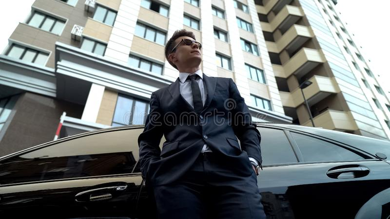 Upset male in expensive suit standing near auto, waiting for business partner. Stock photo royalty free stock photos